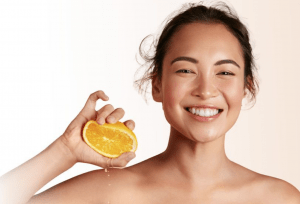 Woman smiling and squeezing an orange in hand